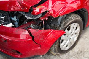 Damaged front bumper of red car